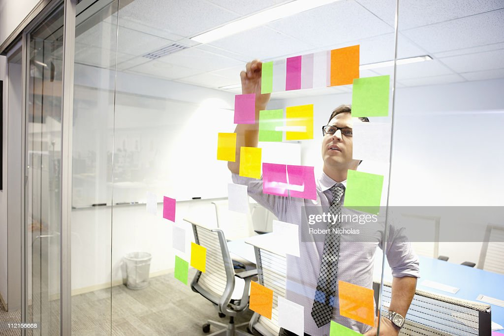 Businessman putting adhesive notes on conference room wall : Stock Photo