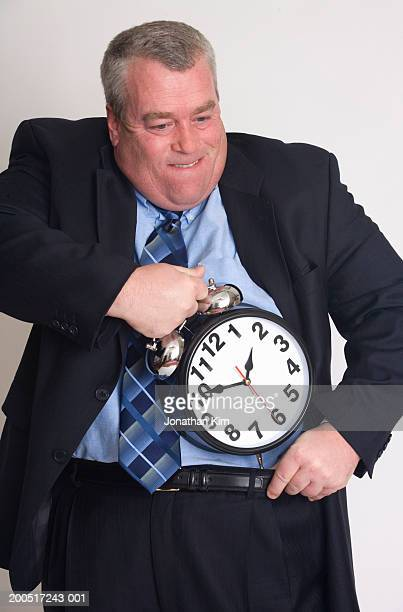 Businessman putting alarm clock in trousers