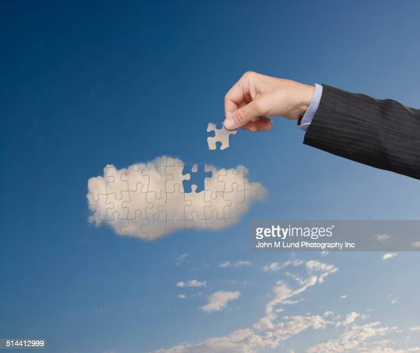 Businessman putting cloud puzzle together