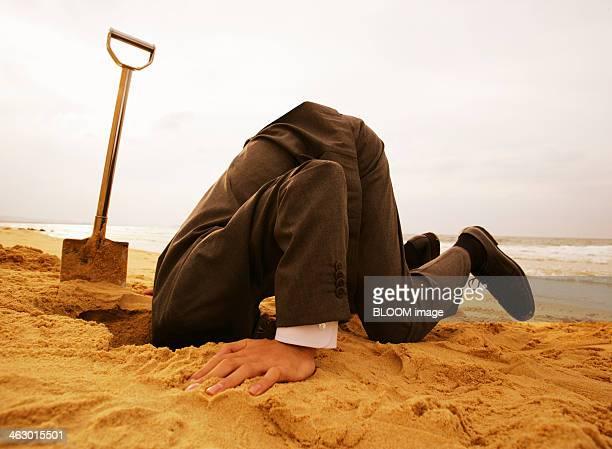 Businessman Putting Head In Sand