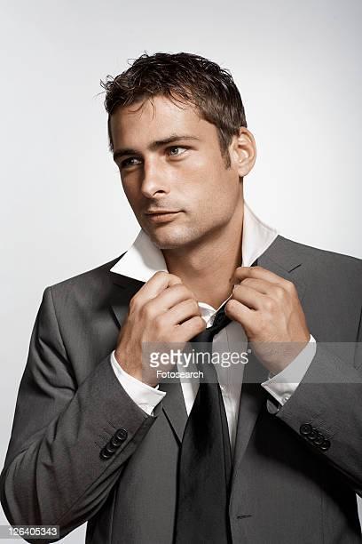 Businessman putting necktie on