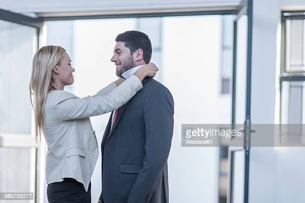 Businessman putting on a tie, woman assisting him