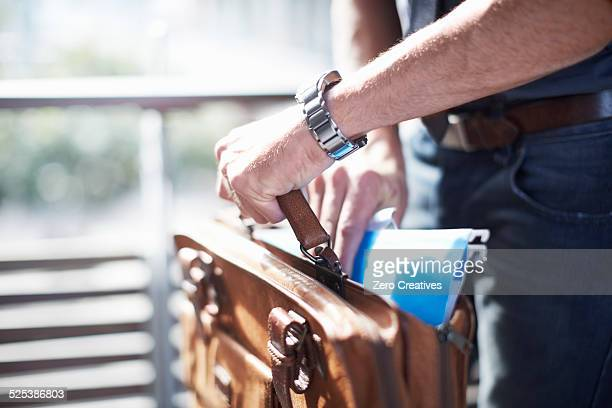 Businessman putting paperwork in briefcase