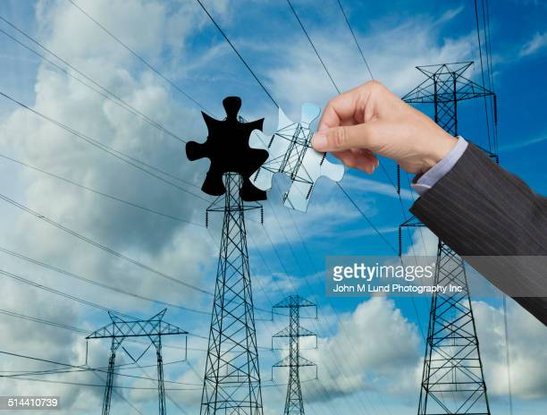 Businessman putting power line puzzle together