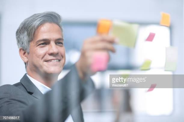 Businessman putting stricky notes on glass pane