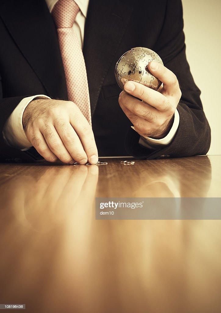 Businessman Putting Together Jigsaw Puzzle Globe : Stock Photo