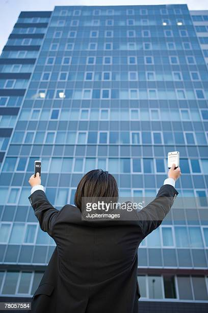 Businessman raising arms up at building and holding cell phone and PDA