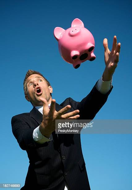 Businessman Reaches Out to Catch Piggy Bank