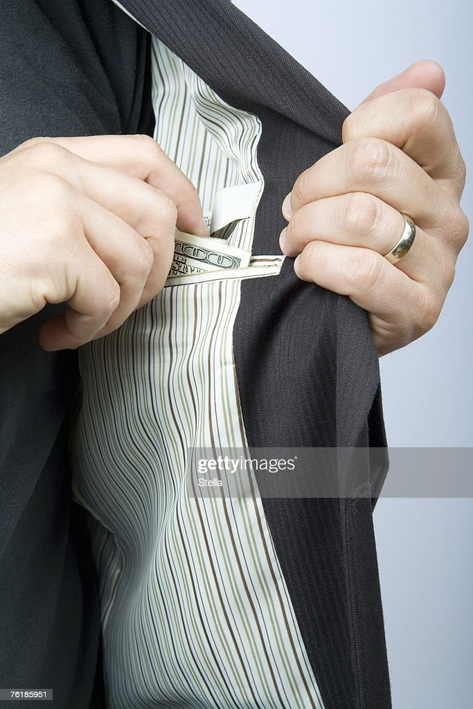 A businessman reaching for money in his suit pocket
