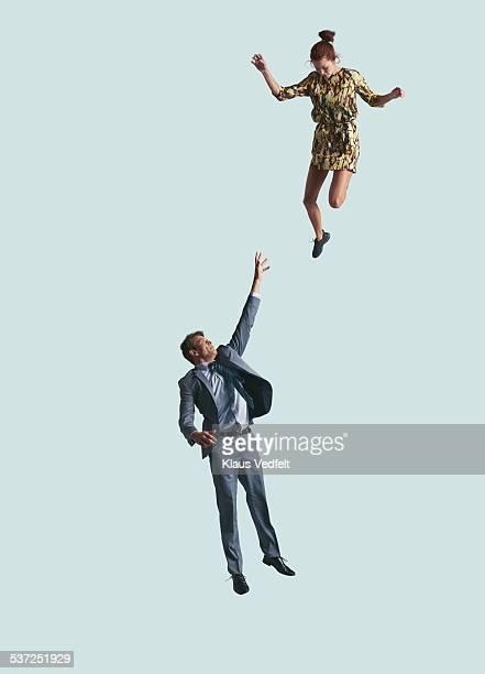 Businessman reaching up in air, woman looking down