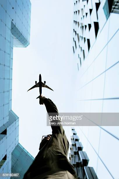 Businessman reaching up to sky towards plane