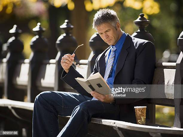 Businessman reading a book in a park