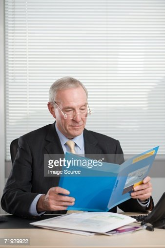 Businessman reading a file : Stock Photo