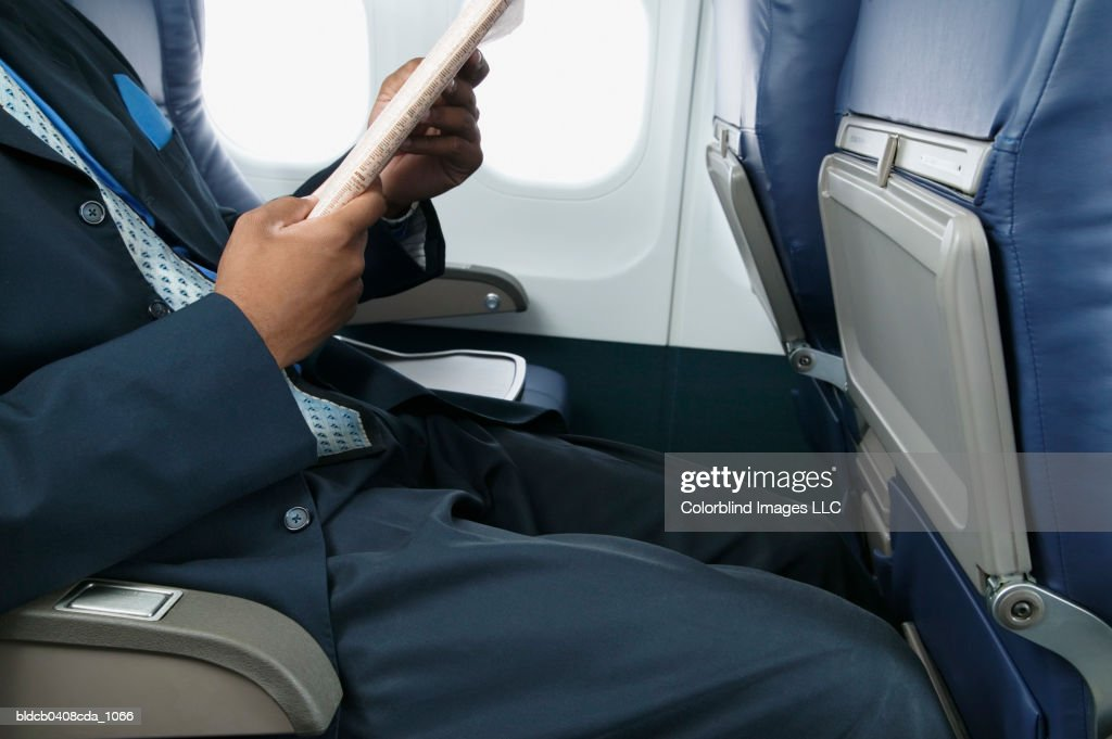 Businessman reading a magazine sitting in an airplane