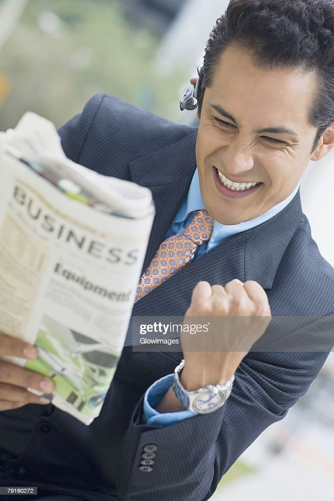 Businessman reading a newspaper and making fists : Stock Photo