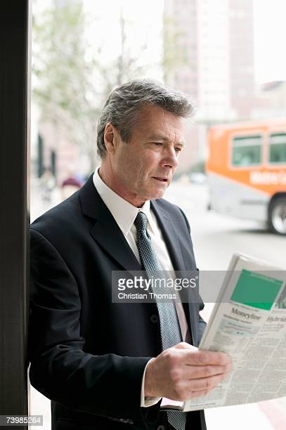 Businessman reading a newspaper at a bus stop