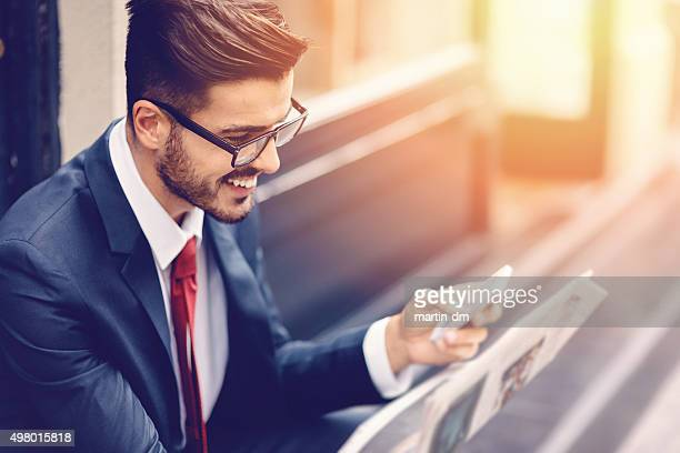 Businessman reading a newspaper at the street