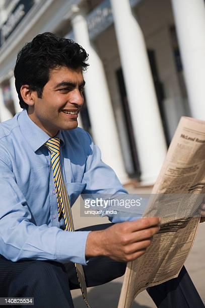 Businessman reading a newspaper, Gurgaon, Haryana, India