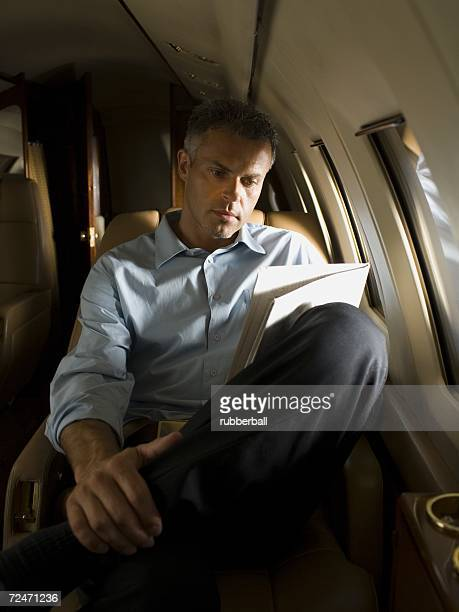 A businessman reading a newspaper in an airplane