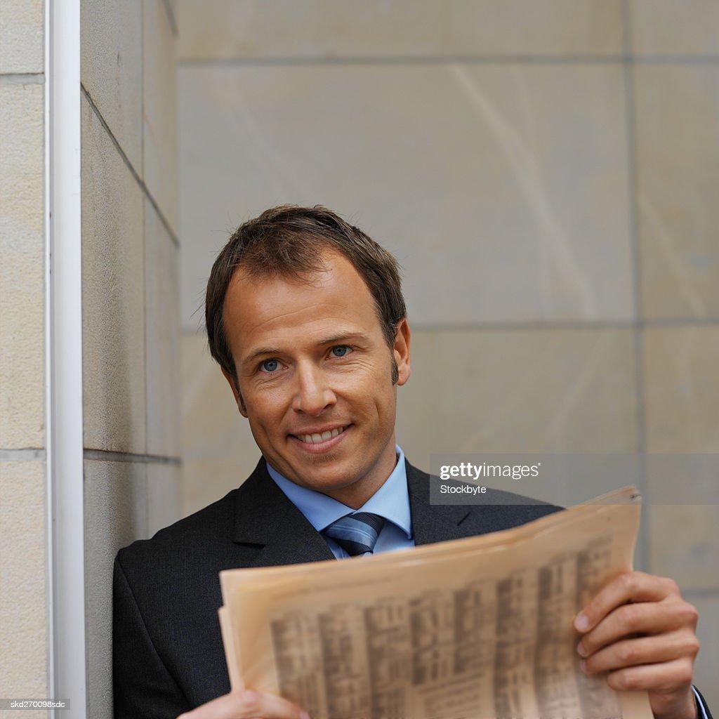 Businessman reading a newspaper : Stock Photo