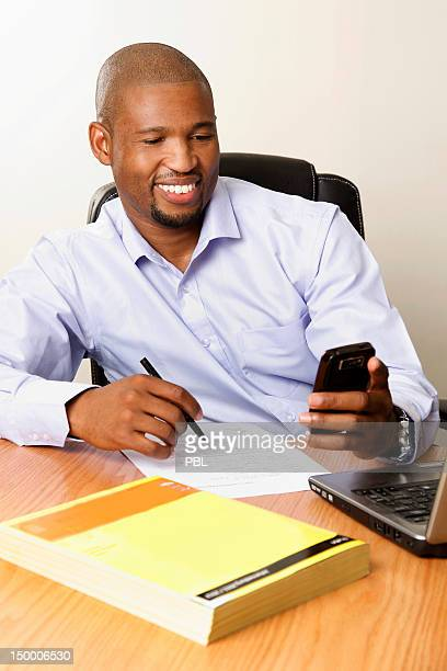 Businessman reading a text message and signing a document.