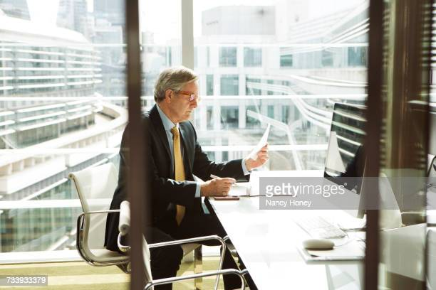 Businessman reading and analysing report, London, UK