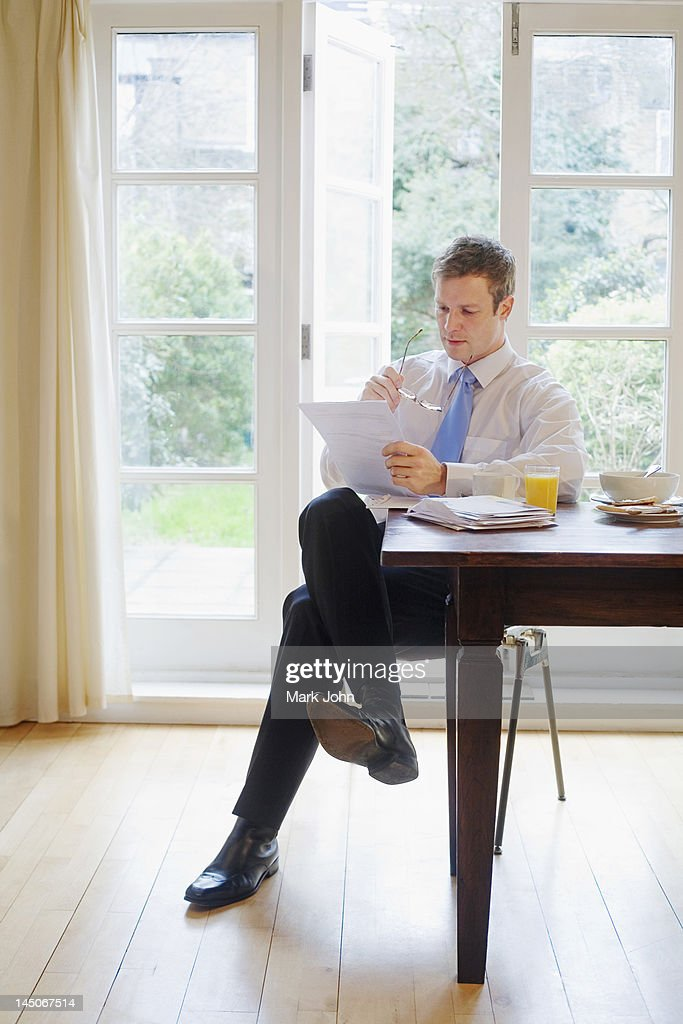 Businessman reading at breakfast : Stock Photo