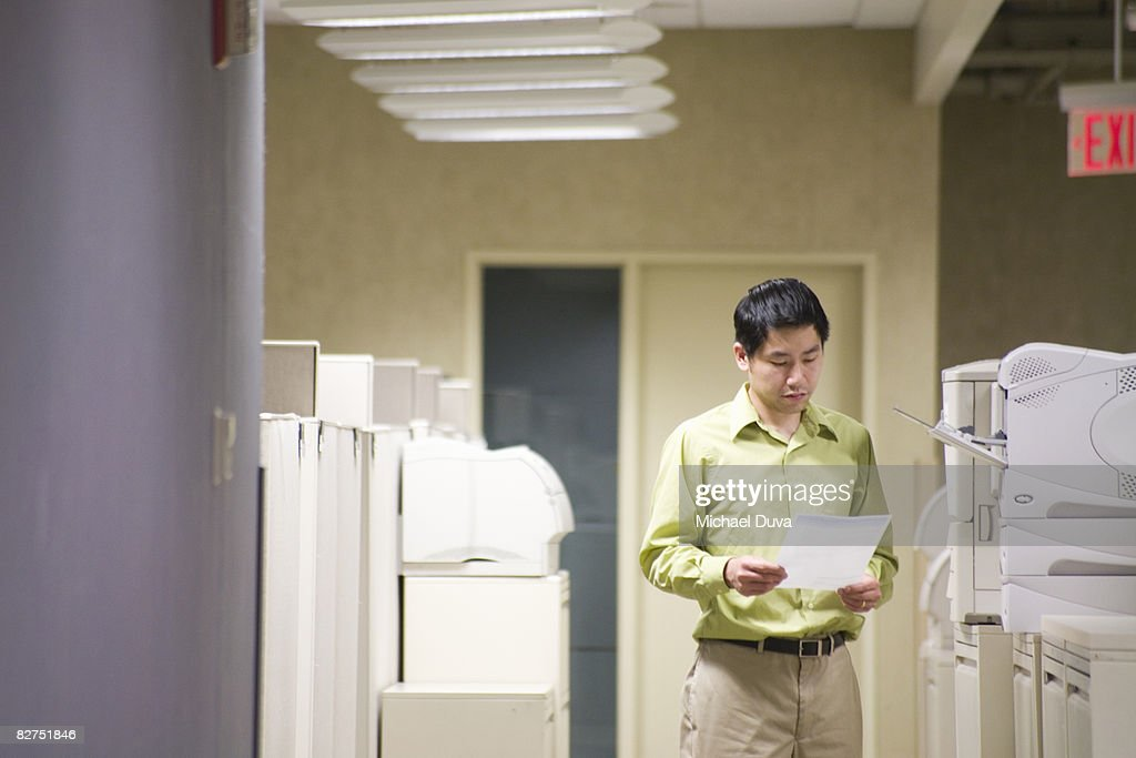 businessman reading at printer station in office