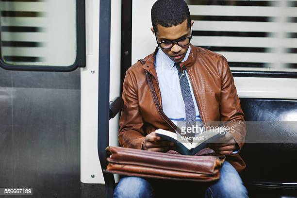 Businessman reading book on the subway train