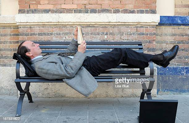 Businessman  Reading  Book Resting on a Bench