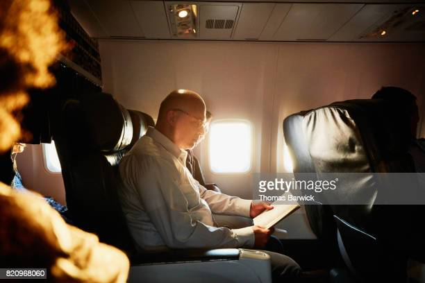 Businessman reading book while traveling on airplane
