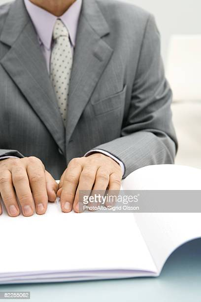 Businessman reading braille document, cropped view
