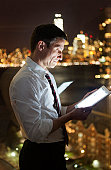 Businessman reading digital tablet with cityscape