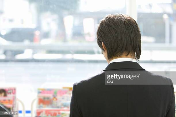 Businessman reading magazine at convenience store