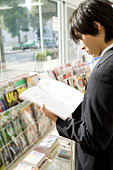 Businessman reading magazine at convenience store