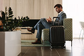 Businessman reading a magazine while waiting for his flight at airline terminal lounge. Entrepreneur at airport waiting area reading a magazine.