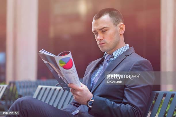 Homme d'affaires, lisant un magazine en plein air
