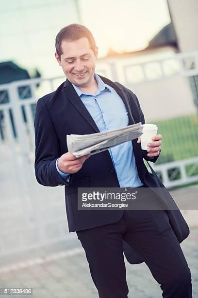 Uomo d'affari leggendo giornali e bere caffè fuori Edificio per uffici