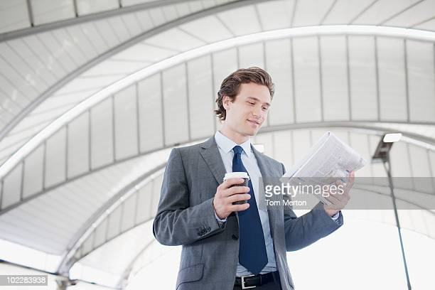 Businessman reading newspaper and holding coffee