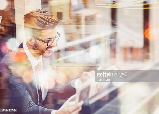 Uomo d'affari leggendo giornali e ricevere tweet e messaggi di testo