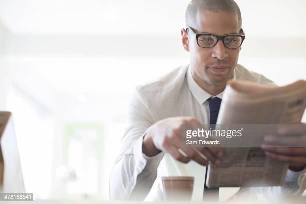 Businessman reading newspaper at breakfast
