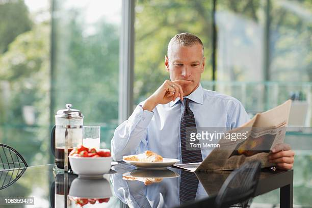 Businessman reading newspaper at breakfast table