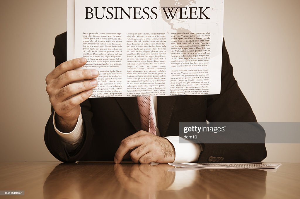 Businessman Reading Newspaper at Desk : Stock Photo
