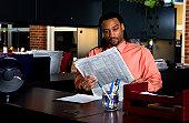 Businessman reading newspaper at his desk