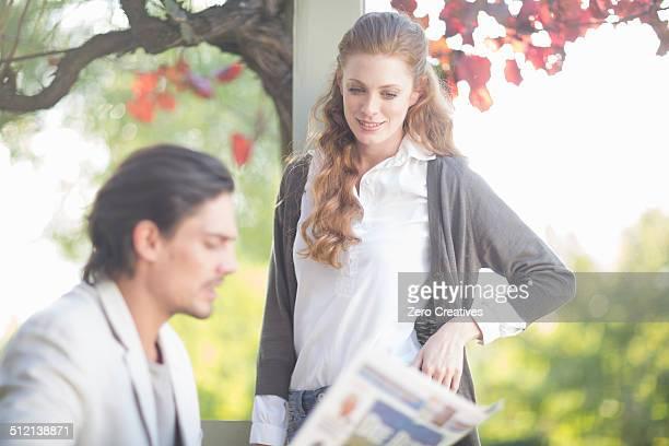 Businessman reading newspaper before informal meeting in garden