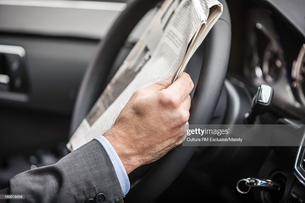 Businessman reading newspaper in car : Stock Photo
