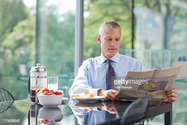 Businessman reading newspaper in morning