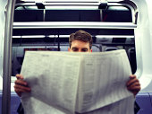 Businessman reading newspaper in subway, close-up