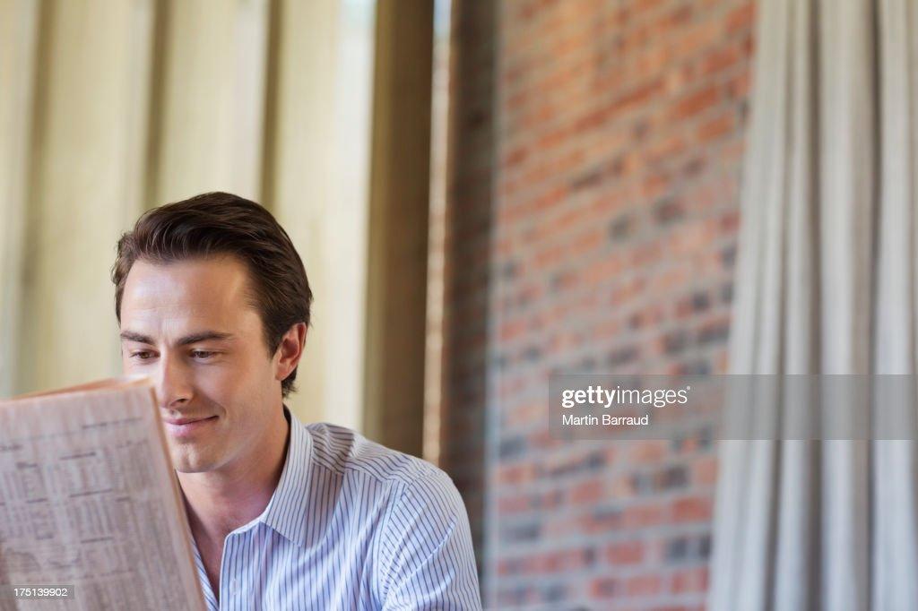 Businessman reading newspaper indoors : Stock Photo