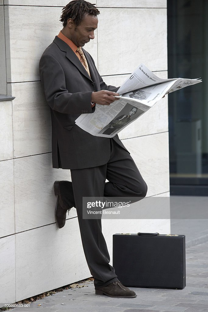 Businessman reading newspaper, leaning against wall : Stock Photo